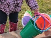 Land-und-Kind.de: Mädchen trägt bunte Sandeimer
