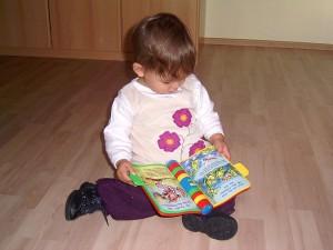 Kleinkind sitzt auf dem Fußboden mit einem Lern- und Spielbuch