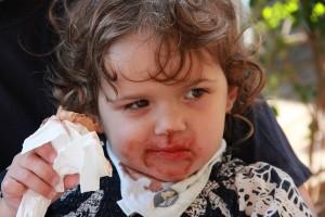 Kleines Kind mit einer Tüte Eis und verschmiertem Schokoladenmund