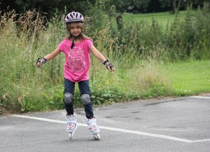 Grundschulkind mit Helm und Knieschützern beim Inline-Skaten