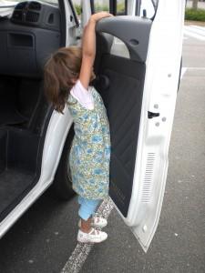 Mädchen hängt an Autotür - Turnübungen während der Reisepause