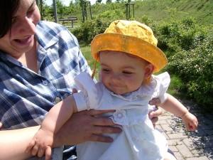 Baby mit Sonnenhut auf dem Schoß der Mutter - Auto-Rast