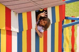 Mädchen winkt aus ihrem Spielhaus