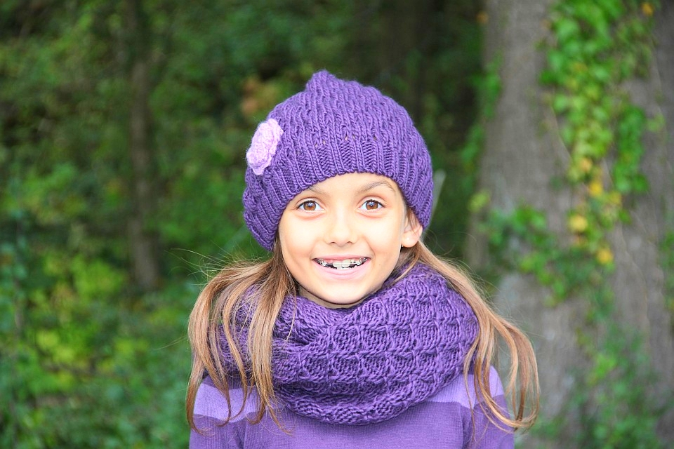 Mädchen mit lila Schal und Mütze