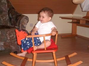 Kleinkind in altem Holz-Schaukelpferd