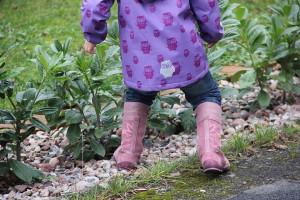 Kind mit Regenmantel und Stiefeln